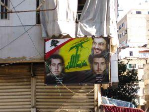 Πανό της Χεζμπολάχ σε σιιτική συνοικία της Βηρυτού. Πάνω δεξιά ο αρχηγός Χασάν Νασράλαχ. Οι δύο νεαροί άντρες είναι πιθανόν μάρτυρες της οργάνωσης.