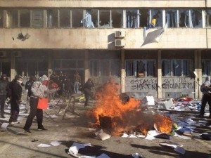 """Εικόνα από την επίθεση σε κυβερνητικό κτίριο της Τούζλα. Το γκράφιτι στους τοίχους του κτιρίου λέει """"Θάνατος στον εθνικισμό"""". Πηγή: revolution-news.com"""