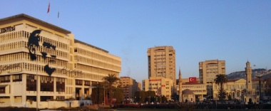 Η κεντρική Πλατεία Διοικητηρίου ή αλλιώς Κονάκι, σημαντική τόσο για την τουρκική όσο και την ελληνική νεώτερη Ιστορία: για τους μεν συμβολίζει την απελευθέρωση από τους Χριστιανούς, στους δε θυμίζει το λιντάρισμα του Μητροπολίτη Χρυσόστομου από το μουσουλμανικό όχλο, που σημάδεψε και το τέλος της χριστιανικής παρουσίας στη Σμύρνη.. Στο κέντρο προς τα δεξιά ο Πύργος του Ρολογιού, στο βάθος πίσω το Όρος Πάγος με το κάστρο, ενώ αριστερά το Δημαρχείο Σμύρνης με την απεικόνιση του προσώπου και της υπογραφής του Ατατούρκ δίνει ίσως και την πολιτική ταυτότητα της πόλης.